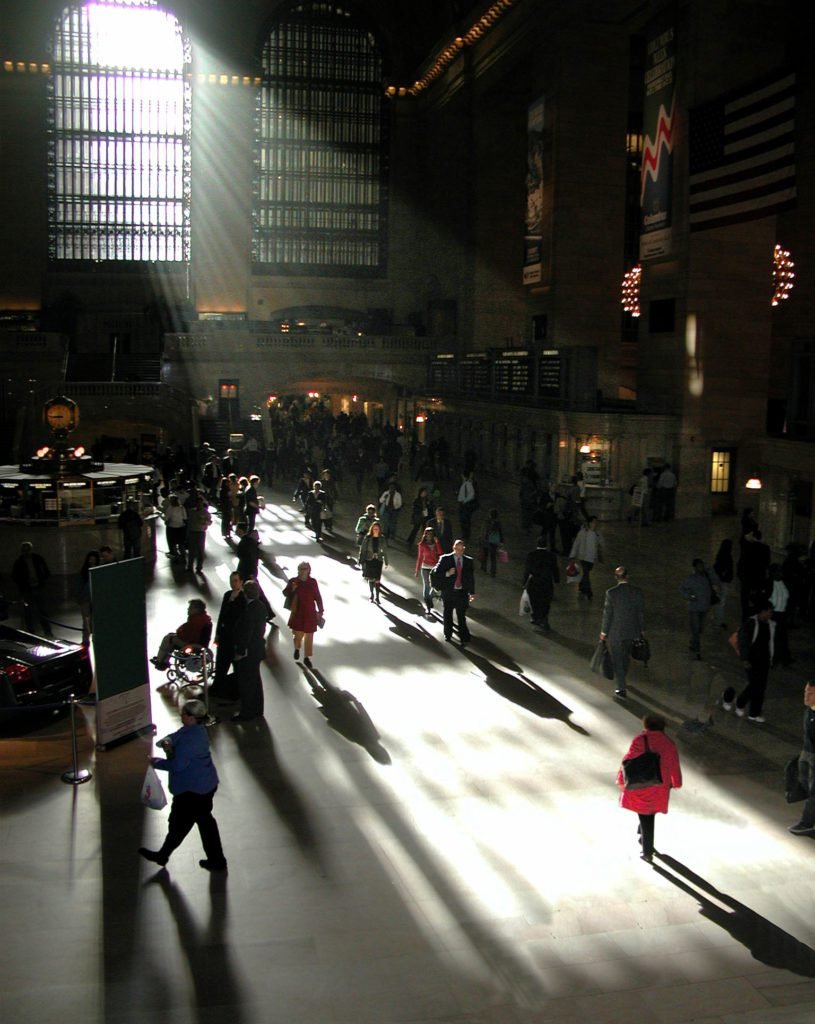 a group of people walking on a city street at night
