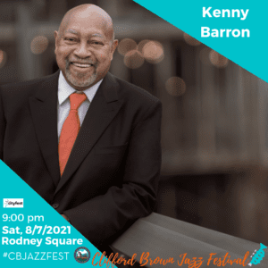 Kenny Barron wearing a suit and tie reading a book