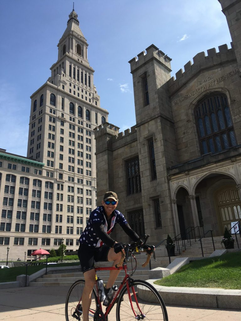 a man riding a bicycle in front of a building